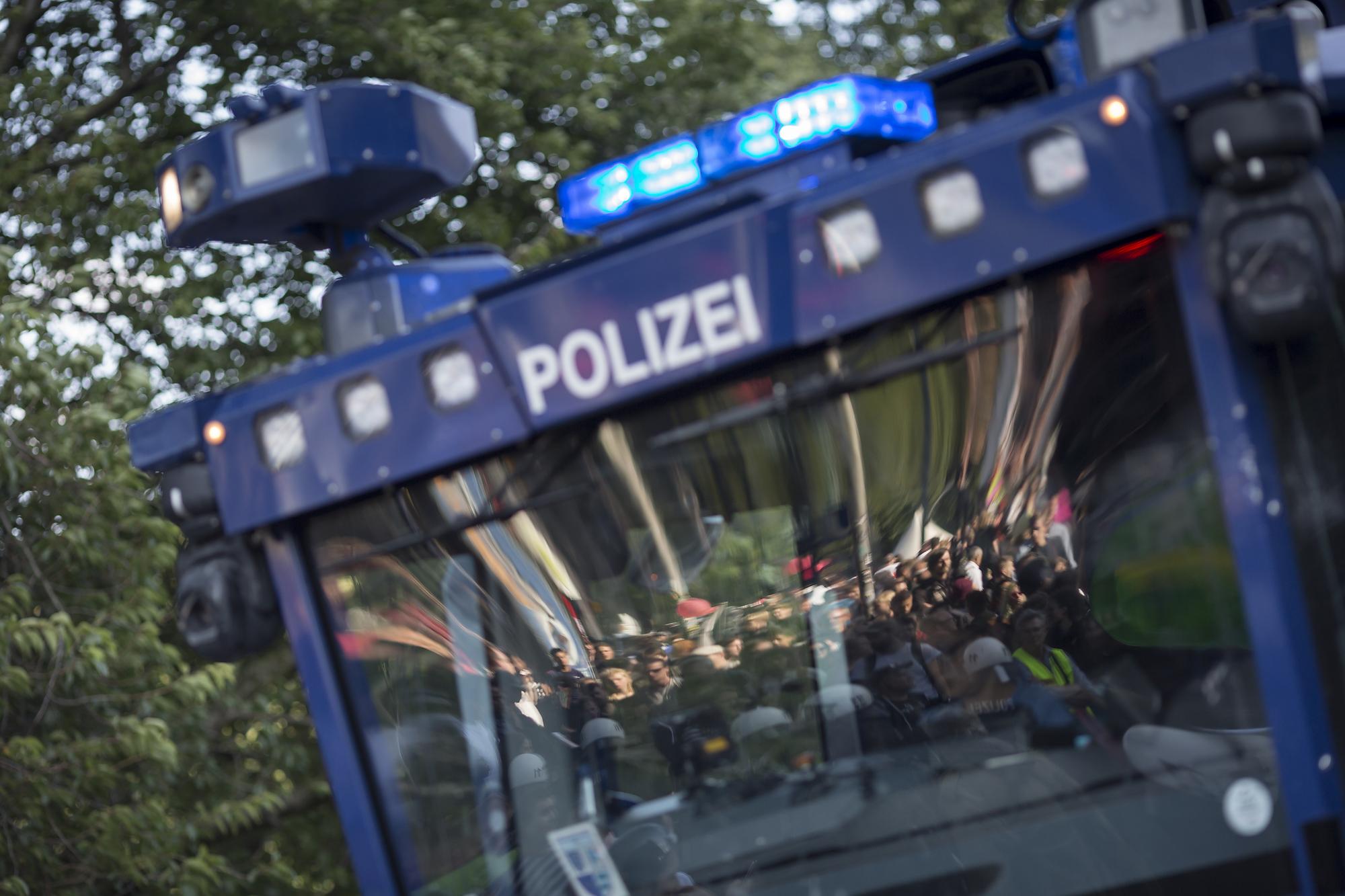 Eine Sitzblockade spiegelt sich am 08/07/2017 in Hamburg bei der Abschlusskundgebung der Großdemonstration gegen den G20 Gipfel in der Scheibe eines Wasserwerfers. Foto Florian Schuh