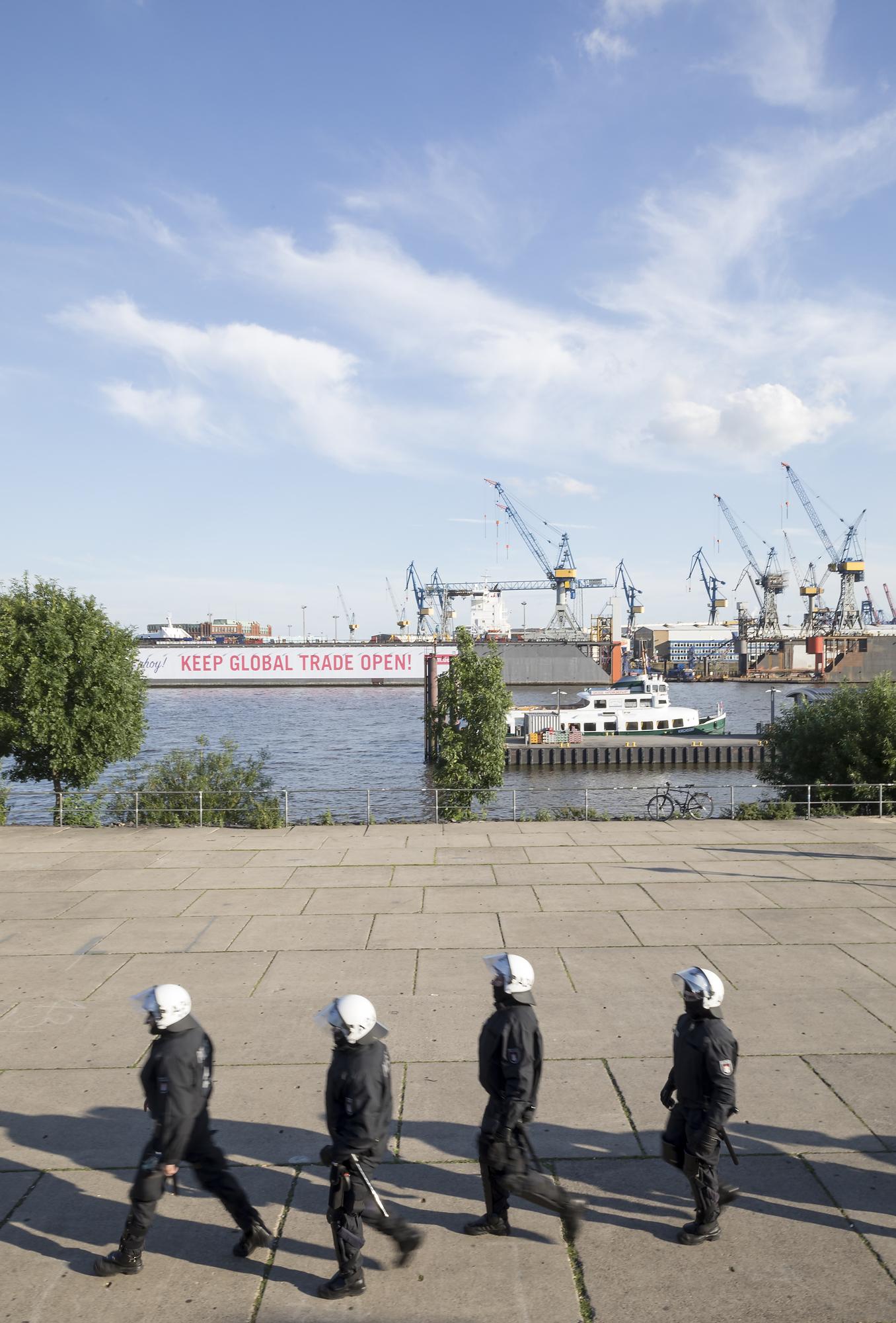 """Polizisten gehen am 06/07/2017 am Fischmarkt in Hamburg vor Beginn der autonomen """"Welcome to Hell"""" Richtung Landungsbrücken, während an den Docks die Forderung """"Keep global trade open"""" zu lesen ist. Foto Florian Schuh"""