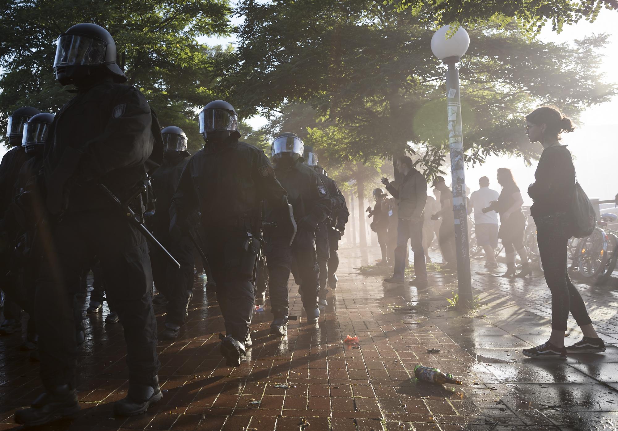 """Polizisten gehen am 06/07/2017 am Fischmarkt in Hamburg nach der uflösung einer Demonstration unter dem Titel """"Welcome to Hell"""" durch die übrigen Demonstranten. Foto Florian Schuh"""