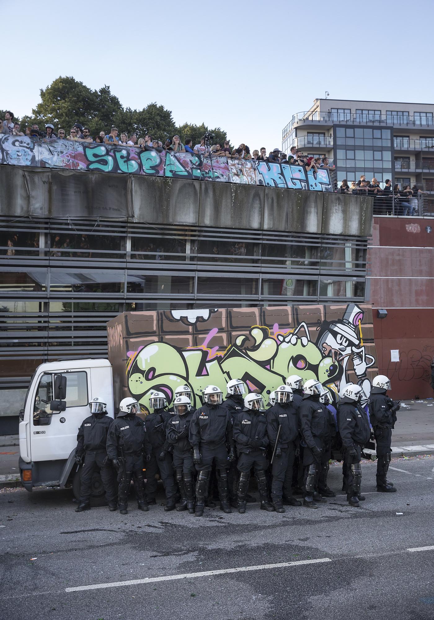 """Polizisten suchen am 06/07/2017 am Fischmarkt in Hamburg nach der Auflösung einer Demonstration unter dem Titel """"Welcome to Hell"""" Schutz hinter einem LKW. Foto Florian Schuh"""