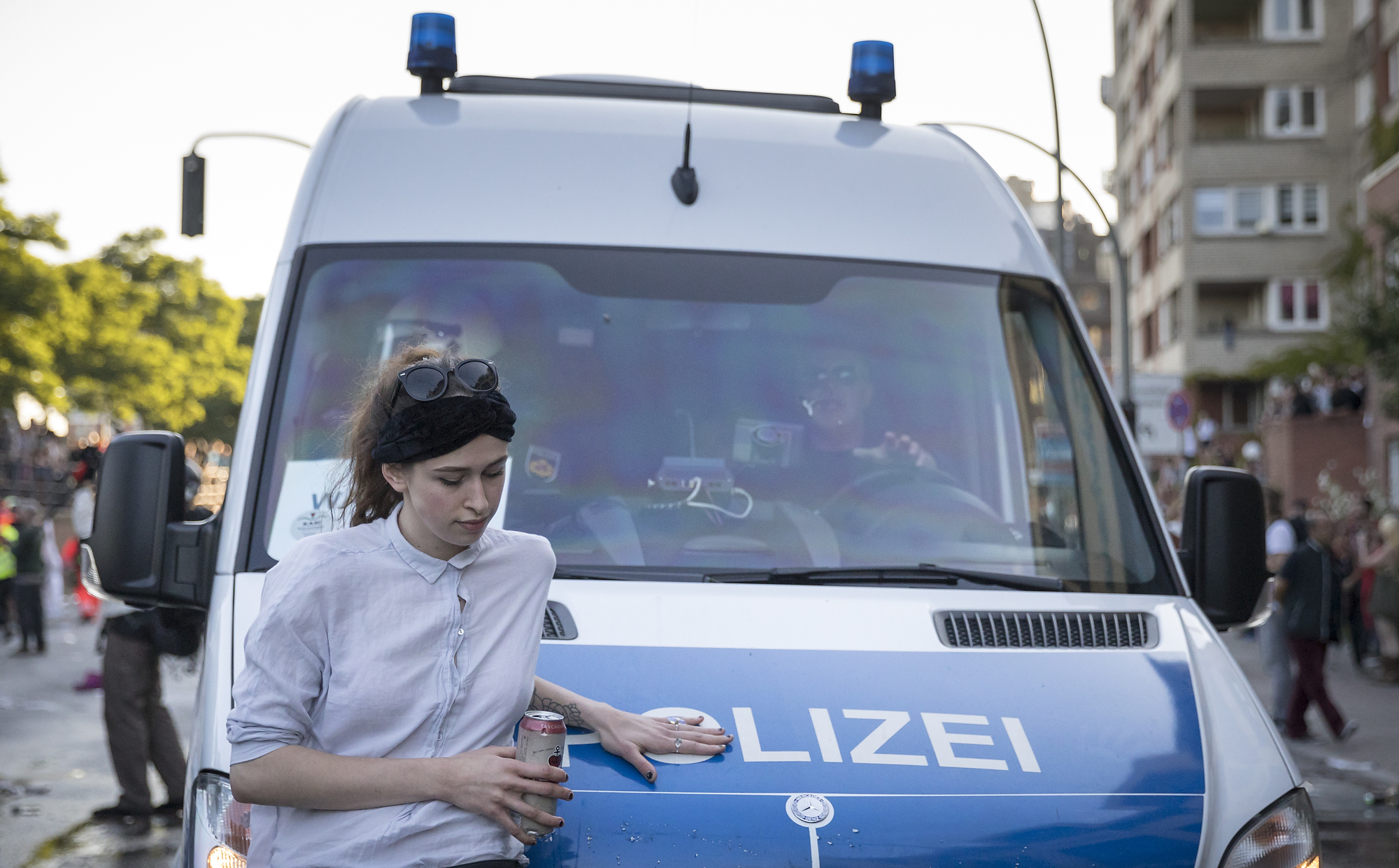 """Eine Demonstrtionsteinehmerin blockiert am 06/07/2017 am Fischmarkt in Hamburg nach der Auflösung einer Demonstration unter dem Titel """"Welcome to Hell"""" ein Polizeifahrzeug. Foto Florian Schuh"""