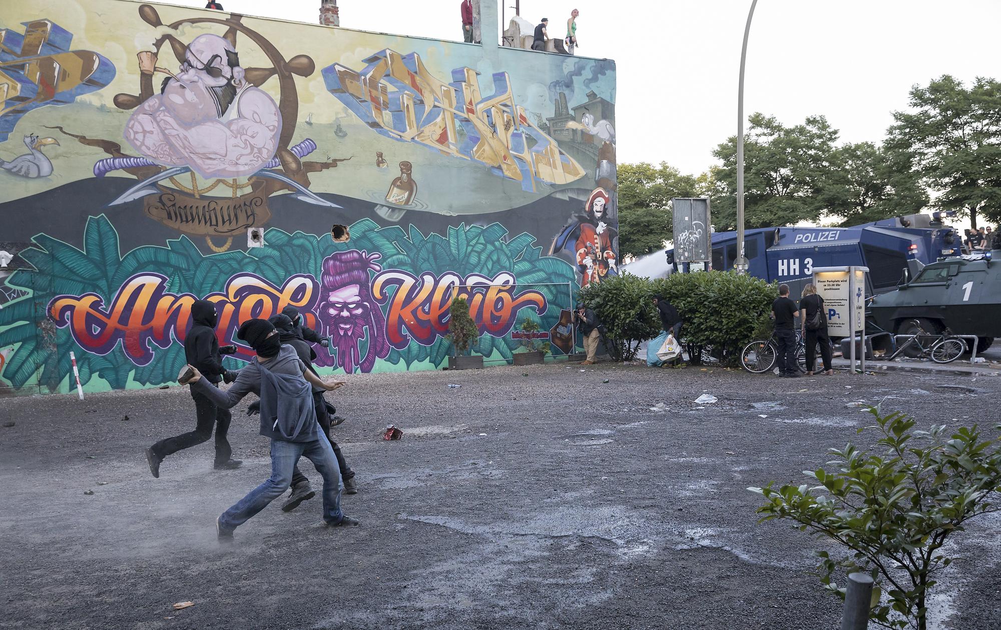 """Vermummte werfen am 06/07/2017 am Fischmarkt in Hamburg nach der Auflösung einer Demonstration unter dem Titel """"Welcome to Hell"""" Steine auf einen Wasserwerfer. Foto Florian Schuh"""