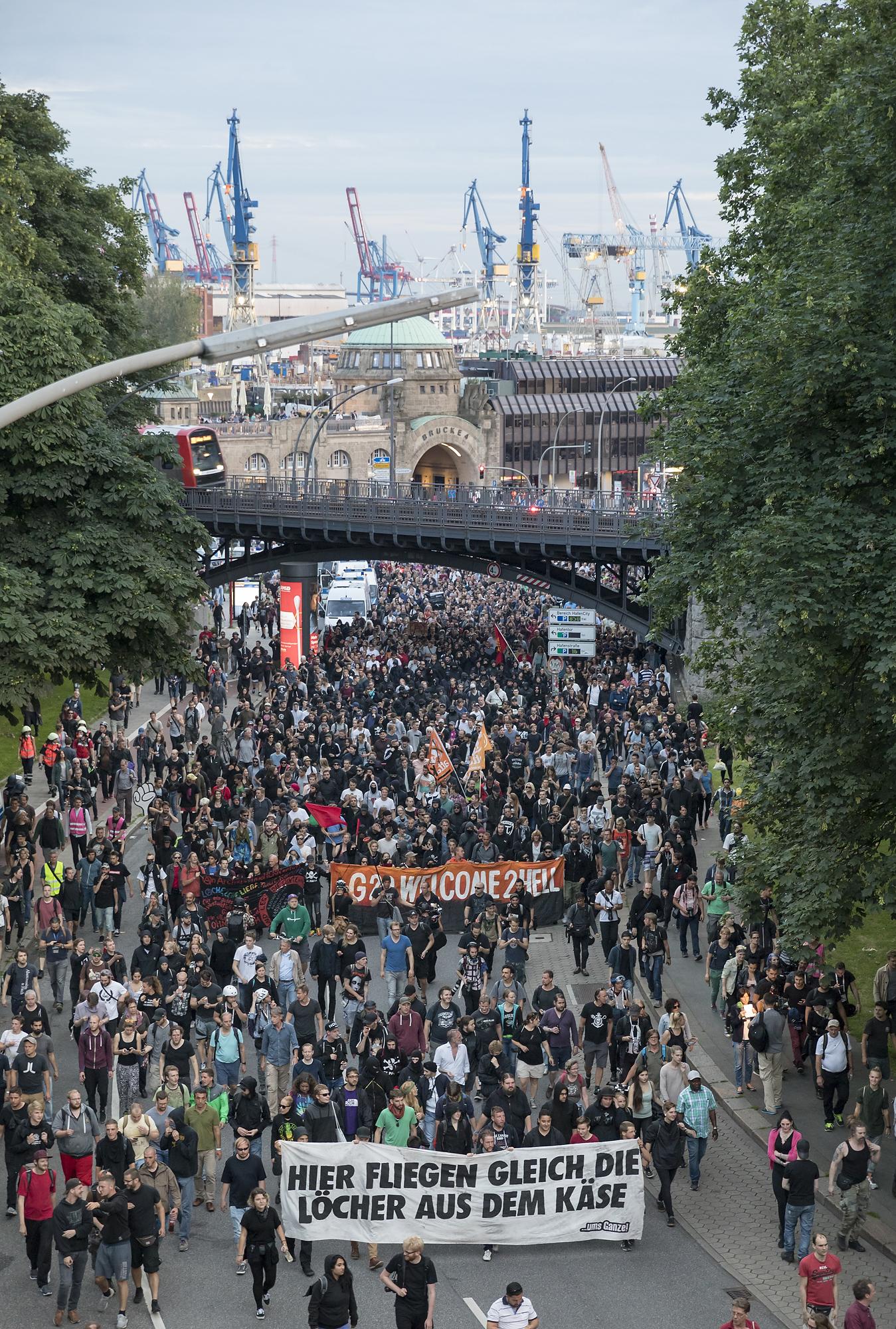 """Demonstranten ziehen am 06/07/2017 am Fischmarkt in Hamburg mit einem zweiten Versuch einer Demonstration unter dem Titel """"Welcome to Hell"""" von den Landungsbrücken Richtung Reeperbahn, während im Hintergrund der Hafen zu sehen ist. Foto Florian Schuh"""