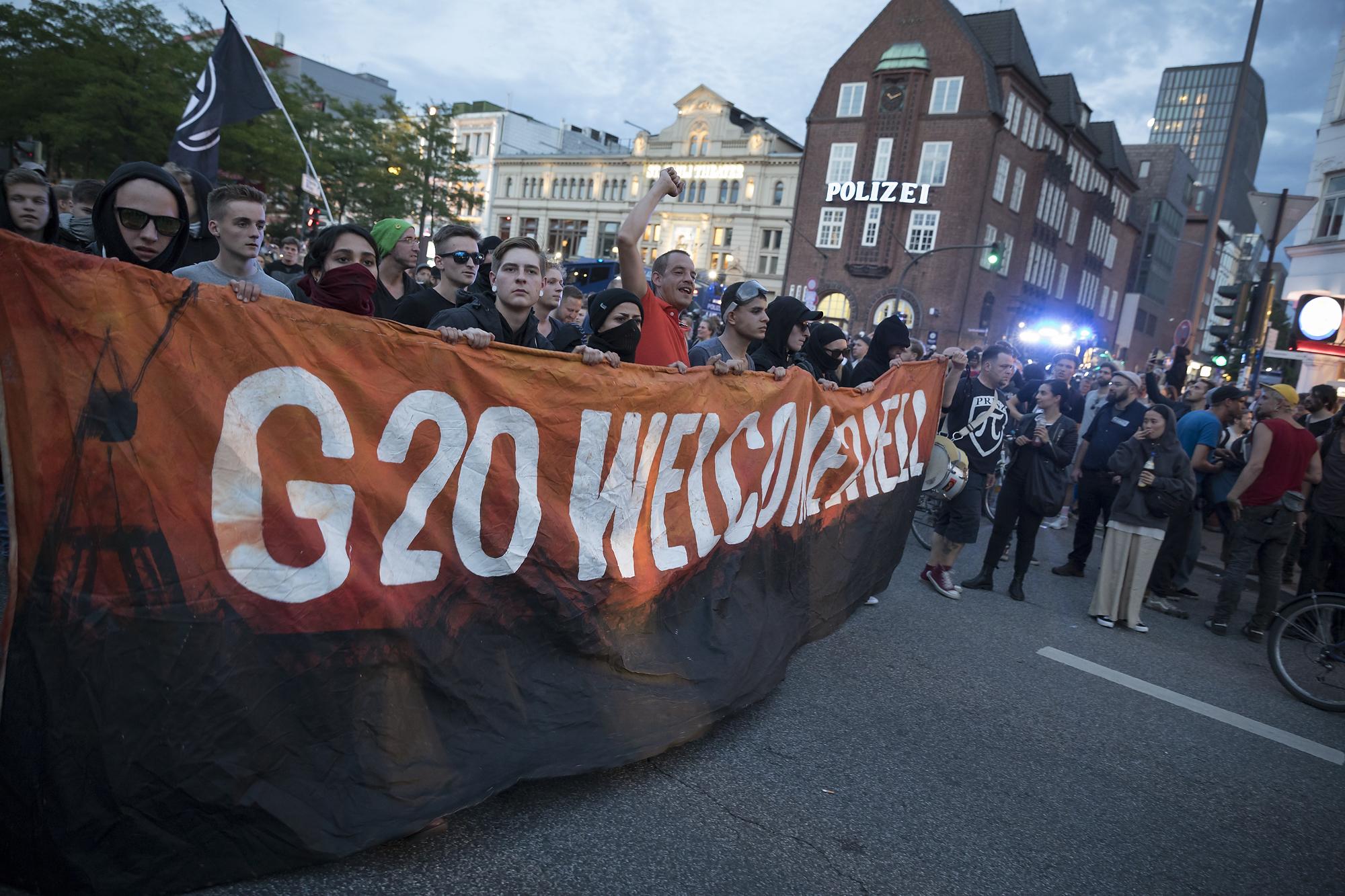 """Demonstranten ziehen am 06/07/2017 am Fischmarkt in Hamburg mit einem zweiten Versuch einer Demonstration unter dem Titel """"Welcome to Hell"""" über die Reeperbahn, während im Hintergrund die Davidwache zu sehen ist. Foto Florian Schuh"""