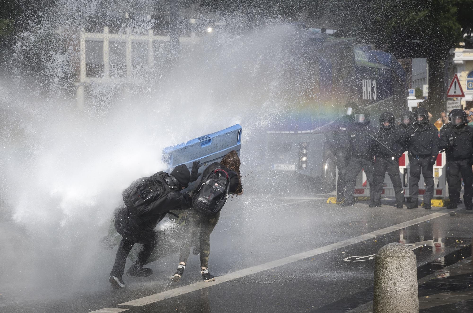 Autonome stellen sich am 07/07/2017 an den Landungsbrücken in Hamburg mit einem Mülleimer dem Strahl eines Wasserwerfers entgegen. Foto Florian Schuh