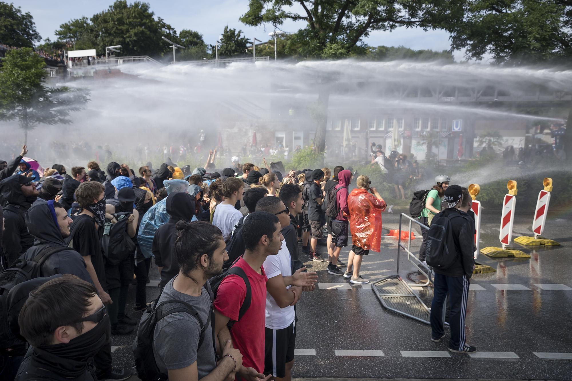 Demonstranten stellen sich am 07/07/2017 an den Landungsbrücken in Hamburg dem Strahl eines Wasserwerfers entgegen. Foto Florian Schuh