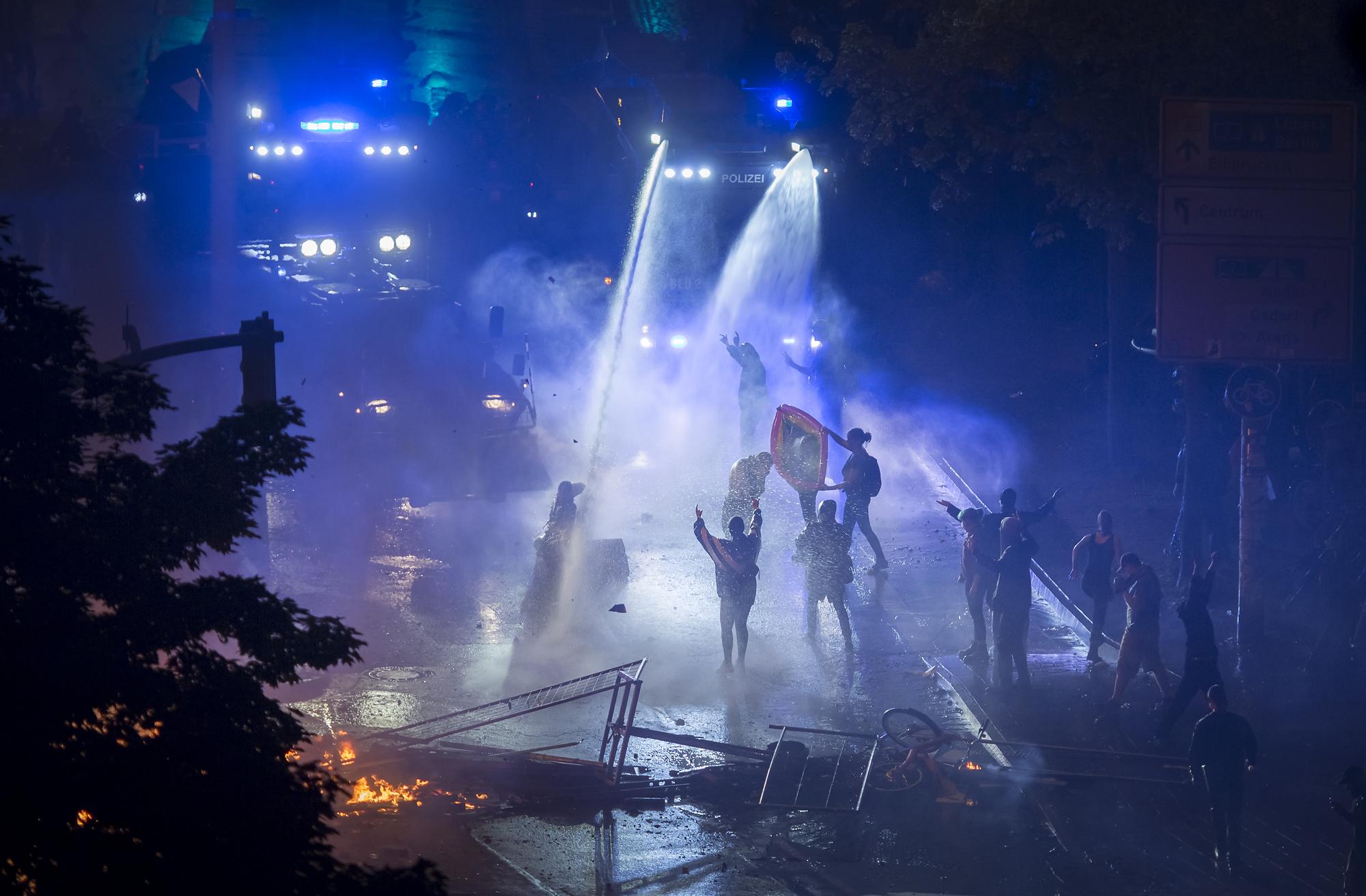 Demonstranten werfen am 07/07/2017 in Hamburg im Schanzenviertel (Neuer Pferdemarkt) Steine auf Wasserwerfer und werden von denen mit Wasser beschossen. Foto Florian Schuh